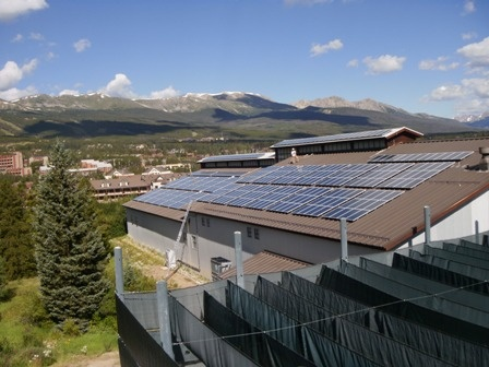 Solar panels placed on the roof of Breckenridge's Ice Arena with mountains in the background