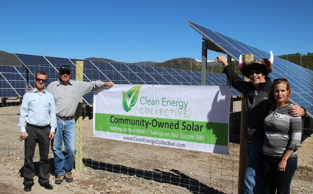 Four people stand in front of solar panels with a banner representing the Clean Energy Collective and Community Owner Solar Gardens